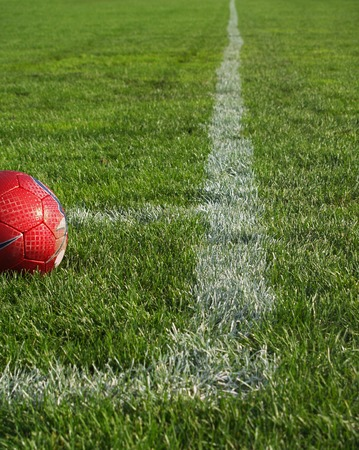 red soccer ball on the grassy field