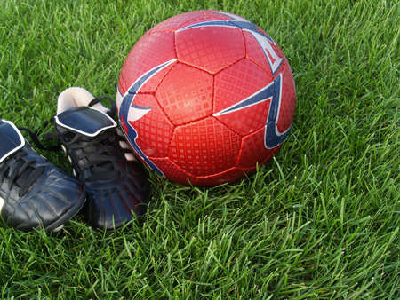 cleats: black soccer cleats and red soccer ball on grass