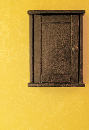 antique key box with crackled paint hanging on a golden wall with faux finish