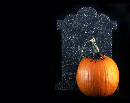 Halloween - orange pumpkin with a spider on top and tombstone behind Stock Photo