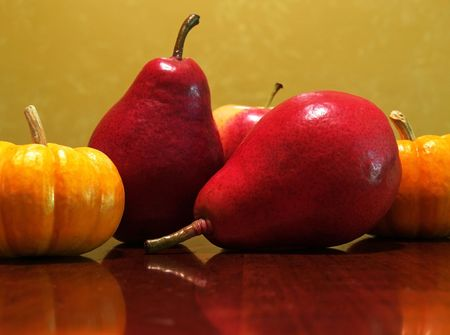 an arrangement of mini pumpkins, red pears and an apple   photo