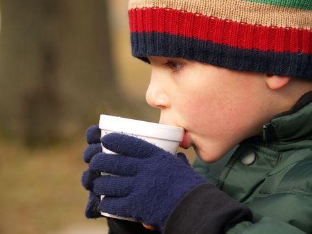 chocolat chaud: jeune gar�on avec chapeau et des gants de boire du chocolat chaud en plein air  Banque d'images