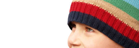 young boys smiling eyes under a striped winter hat  Stock Photo