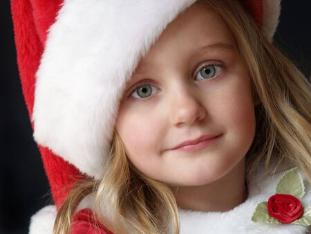 little girl wearing a Christmas dress and Santa hat Stock Photo