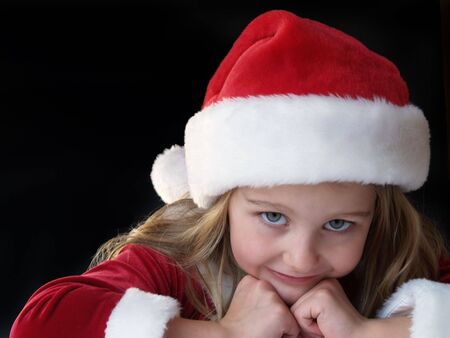 little girl wearing a Santa dress and hat for Christmas