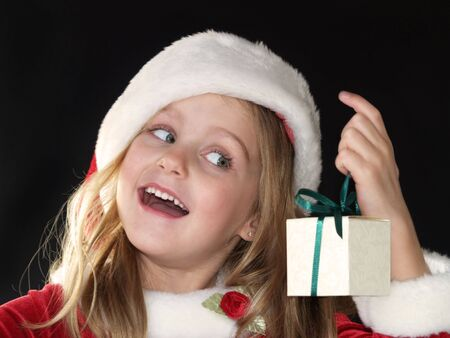 little Christmas girl dressed in Santa hat and dress while holding a gift Stock Photo