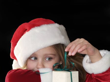 little girl pulling on the ribbon of a Christmas gift
