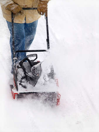 man using a snowblower on a winter day