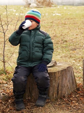 young boy drinking hot chocolate while sitting on a tree stump outside