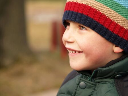 young boy smiling in the outdoors while wearing a winter coat and hat