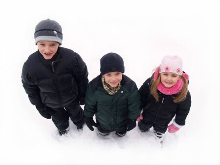 three children in winter clothes standing in the snow photo