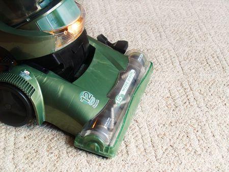 カーペットの抜本的な緑色の掃除機