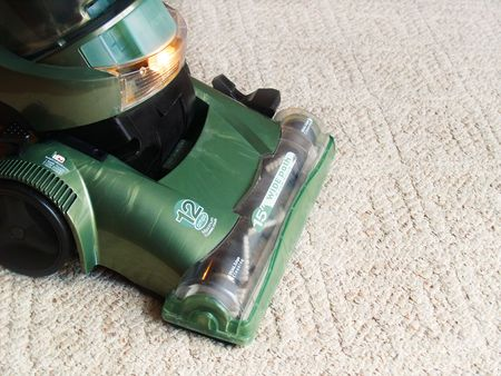 a green vacuum cleaner sweeping the carpet photo