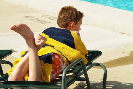 resting: young boy taking a break from swimming and resting on a chaise lounge