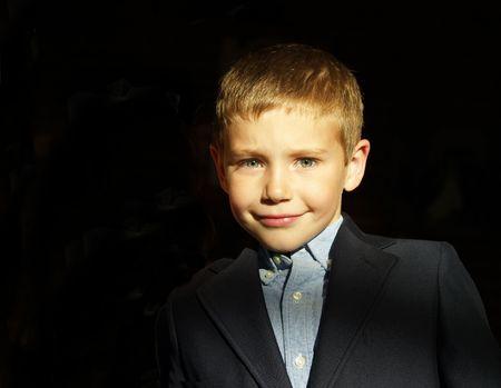 a young boy wearing a blue shirt and blazer