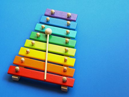 xylophone: a colorful wooden xylophone over a blue background