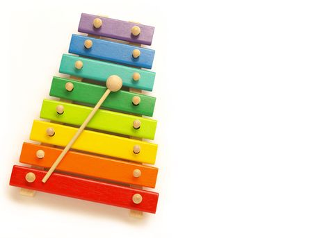 a colorful, wooden xylophone with mallet over white Stock Photo