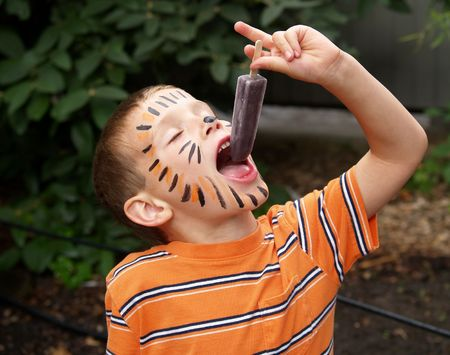 young boy with tiger face paint eating a frozen ice treat Stock Photo