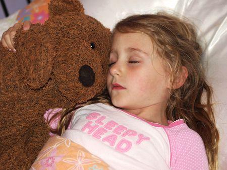 little girl sleeping with her stuffed teddy bear photo