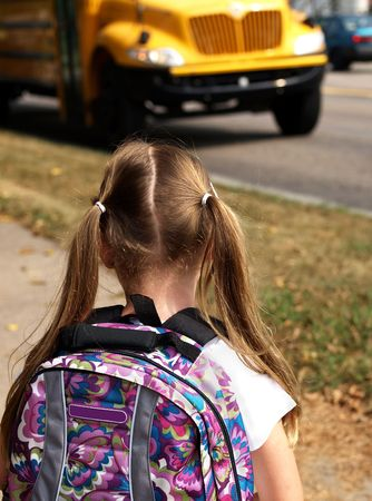 バックパック: 若い女の子を着てバックパックと学校のバスを待っています。
