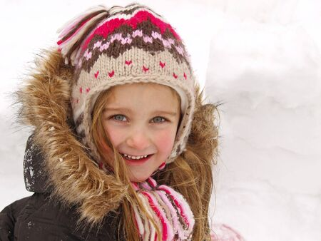 happy little girl playing in the snow Stock Photo