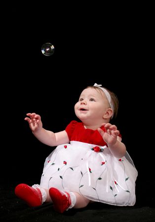 Cute baby girl in a red and white dress, looking up at a single, floating bubble.