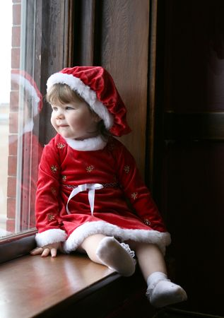Pretty little girl sitting at a large, old fashioned window, wearing a santa-style dress and hat.