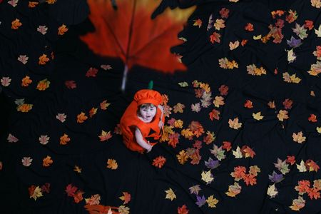 Pretty little girl dressed in a pumpkin costume, watching leaves fall from above; shot from above. Stock Photo - 2983249