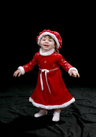 Pretty little girl dressed in a Santa-style dress and hat, standing with her arms out stretched and smiling. Imagens