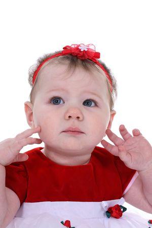 Peuter met heldere blauwe ogen, draagt een rode top en rode haren boeg, met haar vingers aan te raken haar gezicht.