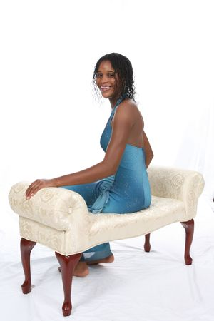 Attractive African American teen wearing a blue sparkly gown, sitting on an ivory bench against a white backdrop. photo