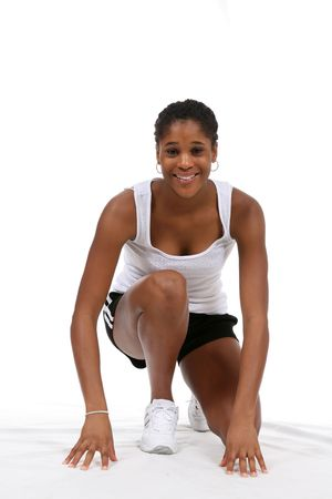 Pretty African American teenage girl, posing in runners starting position and smiling.