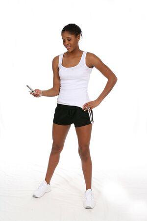 魅力的な十代の携帯電話や服を着て運動