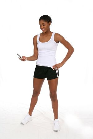 Attractive teen with a cell phone and athletic clothes