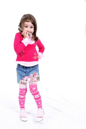 Cute little girl in stylish pink clothing, hand on her hip, holding her cell phone and grinning. Banco de Imagens