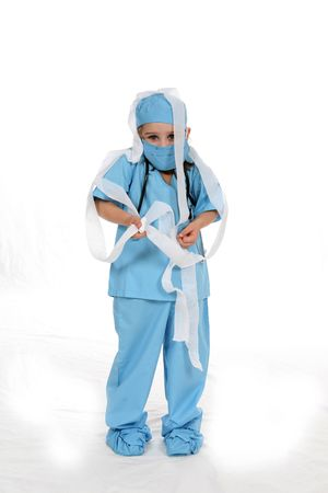 Cute child in medical scrubs with gauze wrapped all over.