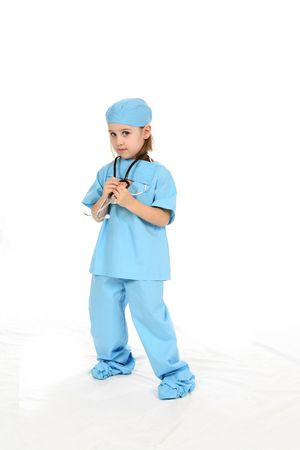 Cute little girl wearing blue scrubs and holding onto a stethescope. Фото со стока