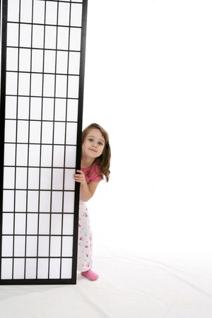 Pretty little girl peeking out from behind a black screen.