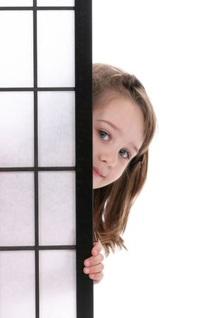four year old: Pretty Little girl peeking out from behind a screen.