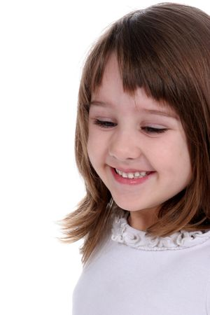 Pretty little girl smiling and looking down; against a white background photo