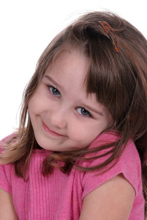 Pretty little girl with a pink shirt; tilting her head to one shoulder and grinning.