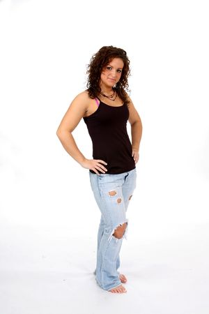 ripped: Attractive teen in ripped jeans, standing with her hands on her hips. Stock Photo