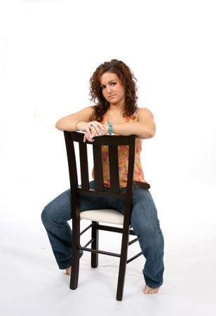 Pretty teen sitting backwards in a chair against a high key background. Stock Photo