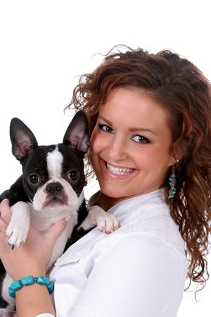 Pretty teenage girl holding a small black and white dog. photo