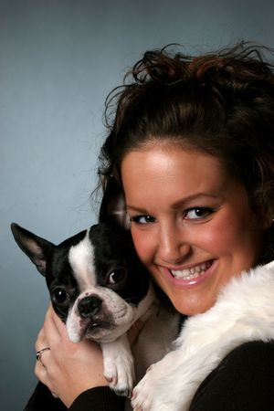 Pretty teenage girl holding her Boston Terrier. photo