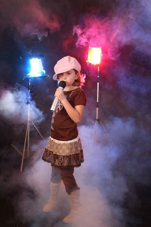 Cute girl singing against a backgrop of colored lights and stage fog.