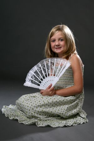 Pretty young girl in a sundress and holding a lace fan. photo