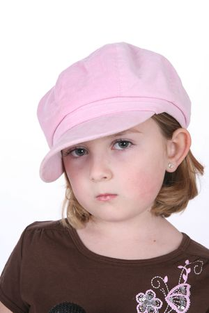 Pretty little girl in a big pink hat with beautiful eyes and a pout. Stock Photo