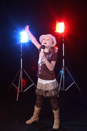 big star: Young girl singing into a microphone against stage lighting. Stock Photo