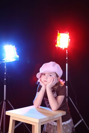きれいな女の子をスツールと舞台照明;腰掛けの彼女の手であご。